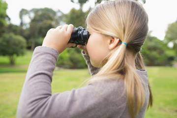 Girl looking through binoculars at park