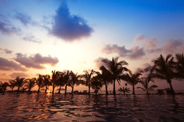 beautiful swimming pool near the beach by sunset