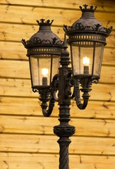 Old street light on the background of wooden wall