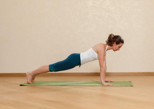 Caucasian woman is practicing yoga at studio (chaturanga dandasa