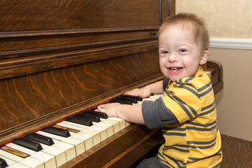 Laughing Down Syndrome boy playing on piano
