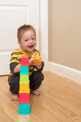 Laughing Down Syndrome boy plays with stacking toy