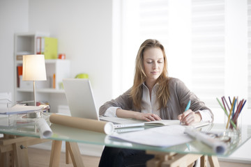 beautiful young woman sitting at her desk in the workplace
