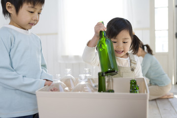 brother and sister separating plastic bottles from bottles