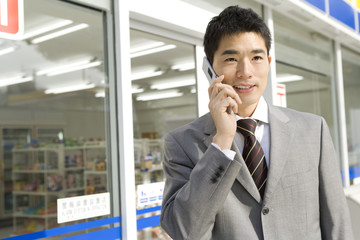 man talking on mobile phone in front of convenience store