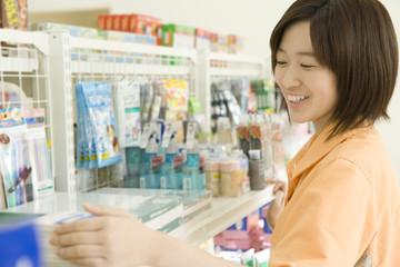 salesclerk of convenience store tidying up goods
