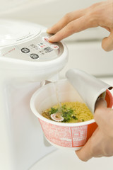 hand of man pouring boiled water into Chinese noodles