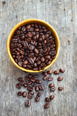 Coffee beans in bowl on wooden background