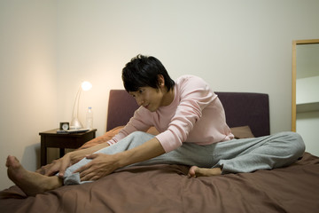 man doing stretch on bed