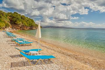 Empty beach Lounge chairs under bright sunlight
