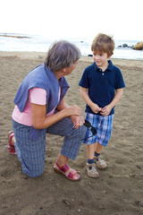 Happy grandmother chatting with grandson on a beach