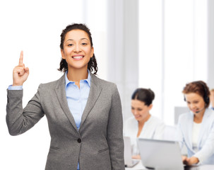 smiling businesswoman with her finger up at office