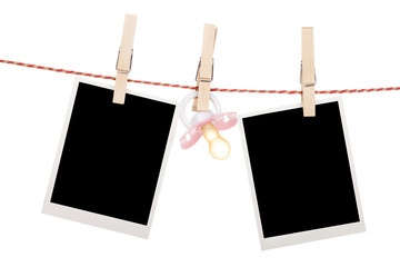 Instant photo frames and pacifier hanging on the clothesline