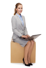 smiling woman sitting on cardboard box with laptop