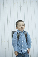 boy carrying a satchel on his back
