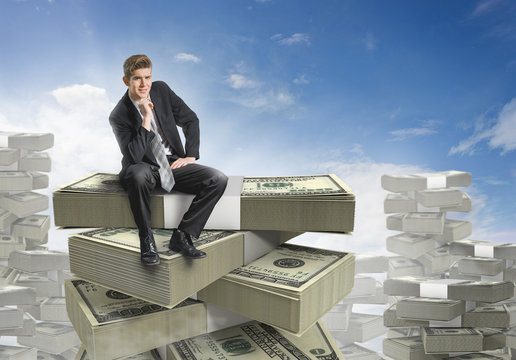 Businessman sitting on a stack of money