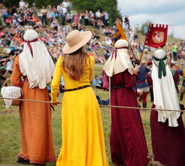 Girls in medieval costumes watching the knightly tournament