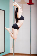 Sexy pole dancer hanging from pole