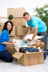 Family, parents, son, unpacking boxes and moving into a new home