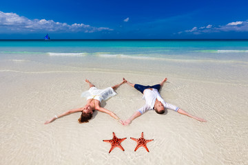 Bride and Groom lying on beach shore with two starfish
