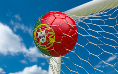 Portugal flag and soccer ball in goal net