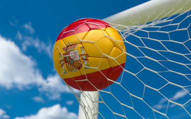 Spain flag and soccer ball in goal net