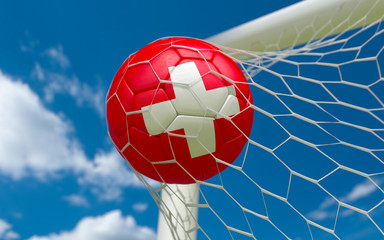 Switzerland flag and soccer ball in goal net
