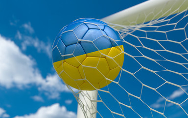 Ukraine flag and soccer ball in goal net