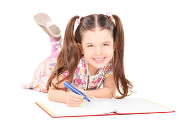 Little girl laying on the floor and drawing in a notebook