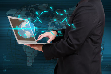 Wall Mural - Businessman holding a laptop with social network icons coming ou