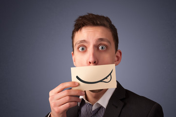 Happy businessman holding funny white card on his mouth