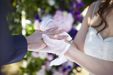 groom placing a ring on his bride's finger