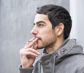 Portrait of man smoking a cigarette, outdoor.
