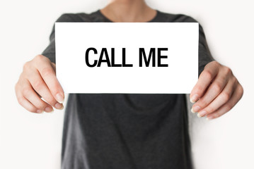 Call me. Female in black shirt showing or holding a card