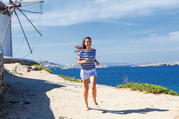 Happy woman running along a coastline near to the windmill.Copy space
