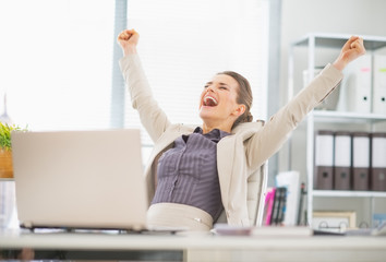 Portrait of happy business woman in office rejoicing success