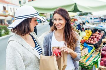 Happy women choosing a fruit outdoors in the bio market