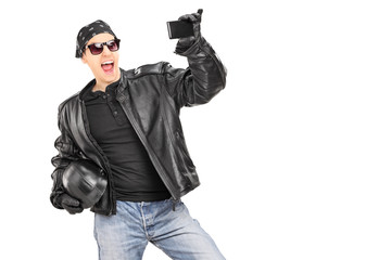 Male biker in leather jacket taking picture of himself