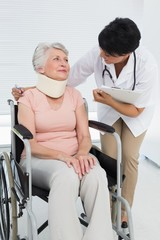 Doctor talking to senior patient in wheelchair with cervical