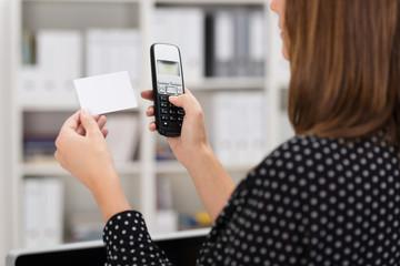 frau im büro mit visitenkarte und telefon