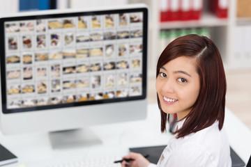 junge mitarbeiterin bearbeitet fotos am computer