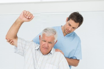 Male physiotherapist assisting senior man to raise hand