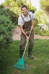 Young man in dungarees raking the garden