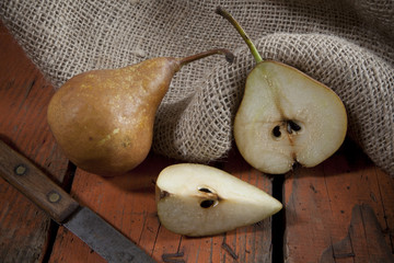 pears on woody rustic table with jute sack
