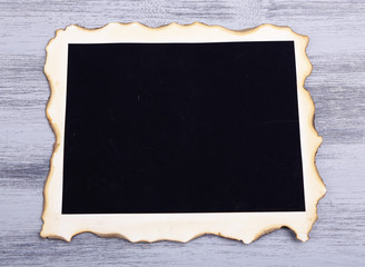 Blank old photo on color wooden background