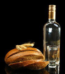 Bottle of vodka, fresh bread and glasses isolated on black