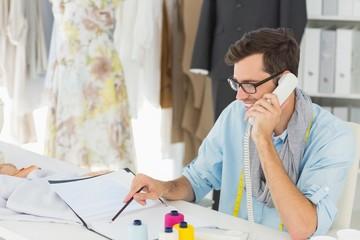 Smiling male fashion designer using phone in the studio