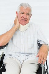 Senior man sitting in wheelchair with cervical collar