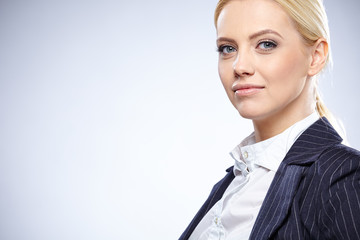 Business woman in a black suit, isolated on grey background