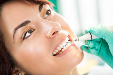 Dentist examination and cleaning patient teeth